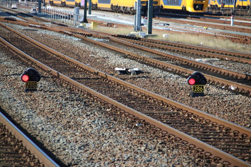 Red signs between the railroad tracks at Rotterdam Central Station in the Netherlands. royalty free stock photo