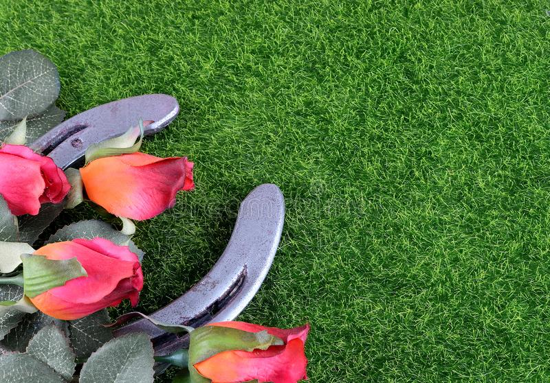 Red silk roses, a horseshoe and artificial green grass for the running of the thoroughbred race called the Kentucky Derby. stock photo