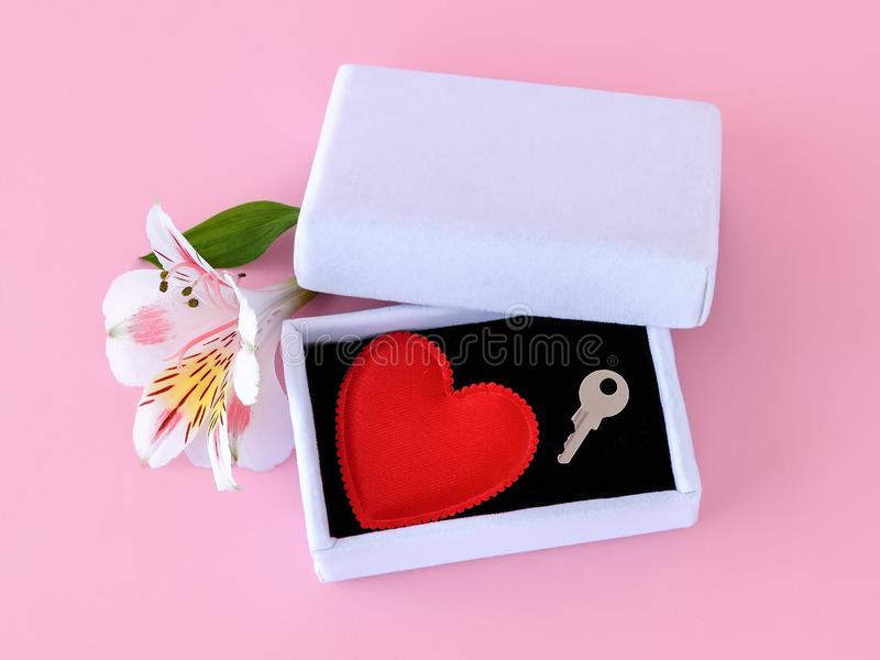 Red silk Valentine heart and a key on black velvet into a white jewelry gift box on a pastel pink background. Key to my heart royalty free stock photography