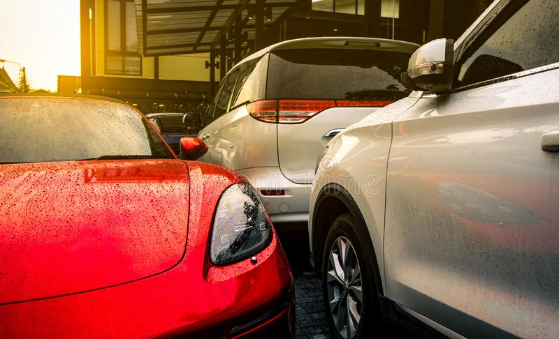 Red and silver car parked on outdoor concrete parking lot of the hotel, home, or apartment. Electric or hybrid car technology. Parking space for rent business royalty free stock images