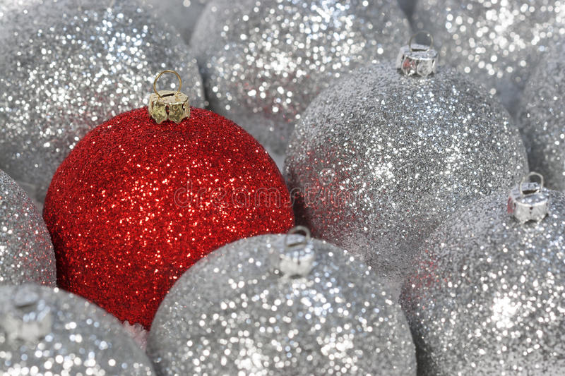 Red Silver Christmas Ornaments. A grouping of silver Christmas ornaments with one glittery red ornament in the group. A concept for being unique or different royalty free stock images