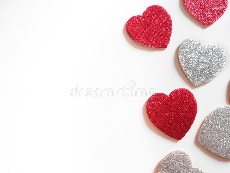 Red and silver glitter hearts on white background. stock image