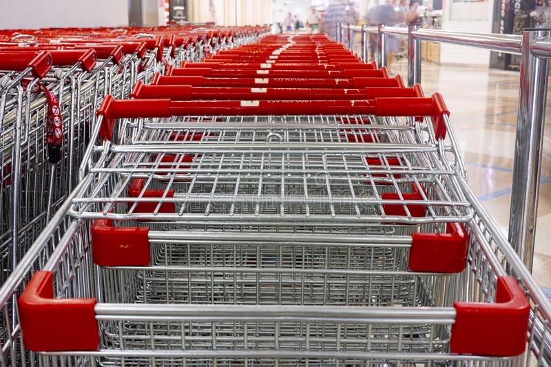 Red and silver shopping trolleys in shopping mall stock photography