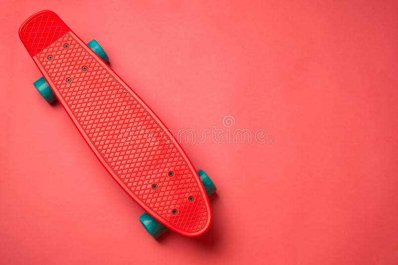 red skateboard with blue wheels on pink background. pastel creative concept. minimalism. flat lay stock image