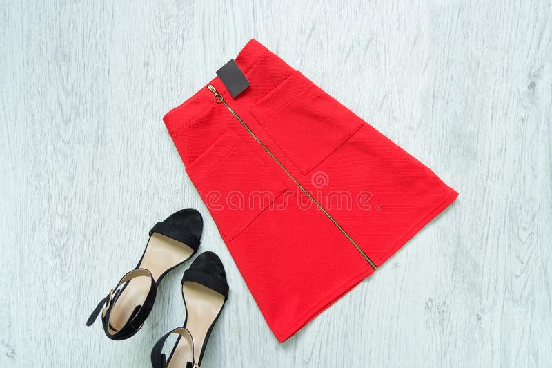 Red skirt with tag and black shoes. Fashionable concept. Red skirt with tag and black shoes. Fashionable concept royalty free stock images