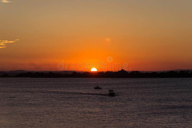 A red sky with the big sun over the river. This is the best sunset in brazil. A big circle sun over the river royalty free stock photography