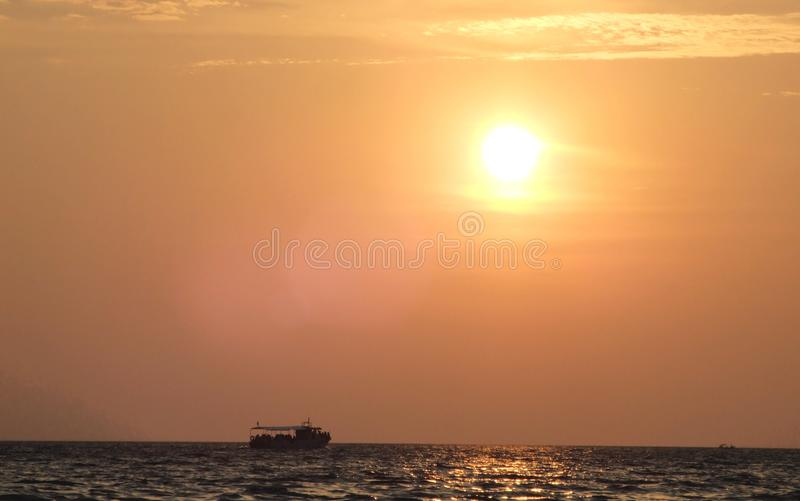 See sunset with a tiny boat at the horizont. Red sky with a few clouds at the sea cost. the end of the day resting and a tiny fishermen boat crossing the royalty free stock photos