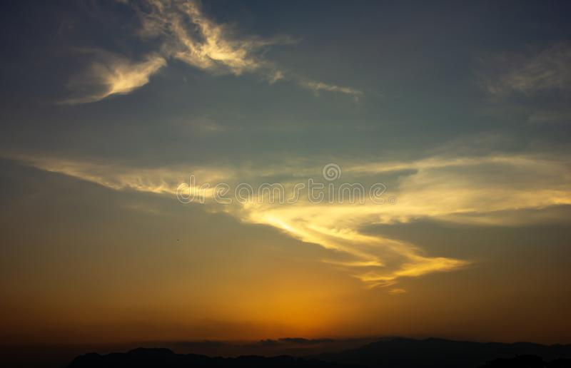 Red sky sunset on moutains.Cloud shaped like S, like a superman. Background royalty free stock photo