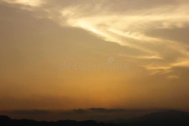 Red sky sunset on moutains.Cloud shaped like S, like a superman. Background royalty free stock image