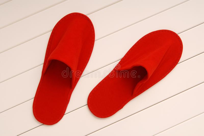 Red slippers from hotel, red slippers from airplane is on white stock image