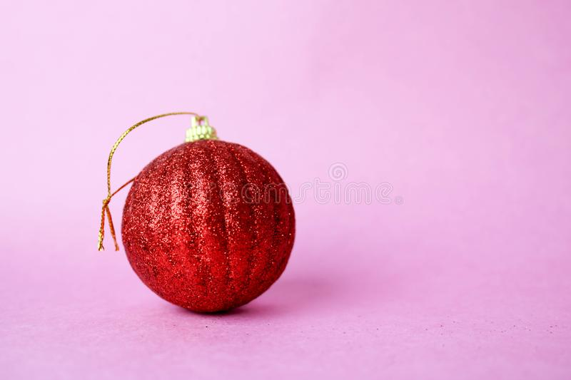 Red small round xmas festive Christmas ball, Christmas toy plastered over sparkles on a pink purple background. Red small round glass plastic winter smart shiny royalty free stock images