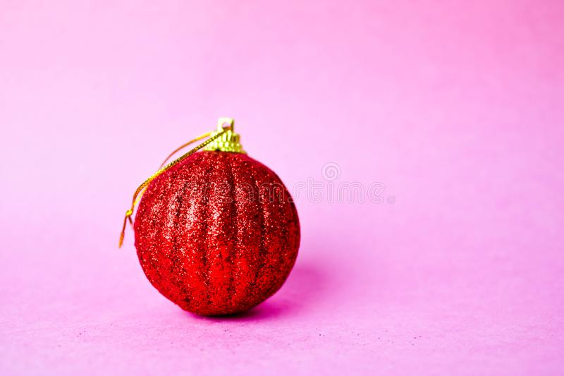Red small round xmas festive Christmas ball, Christmas toy plastered over sparkles on a pink purple background. Red small round glass plastic winter smart shiny royalty free stock photos