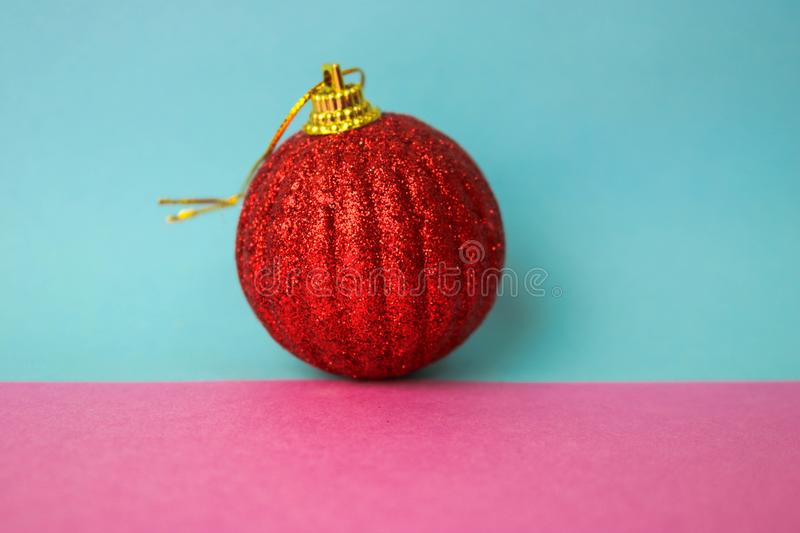 Red small round glass plastic xmas festive Christmas ball, Christmas toy plastered over sparkles on a pink purple blue background. Red small round glass plastic royalty free stock photos