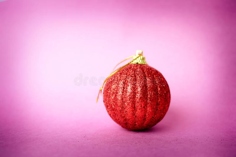 Red small round xmas festive Christmas ball, Christmas toy plastered over sparkles on a pink purple background. Red small round glass plastic winter smart shiny stock photo