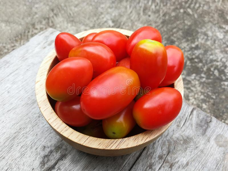 Small tomato. Red small tomato in wood cup stock photography
