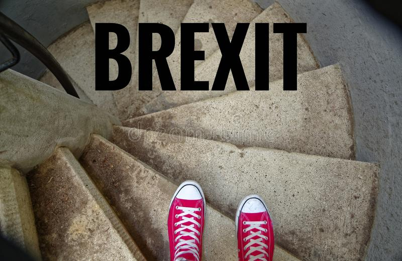 Red sneakers on spiral staircase when going downhill with inscription Brexit symbolizing the withdrawal of Great Britain from the. EU stock photos