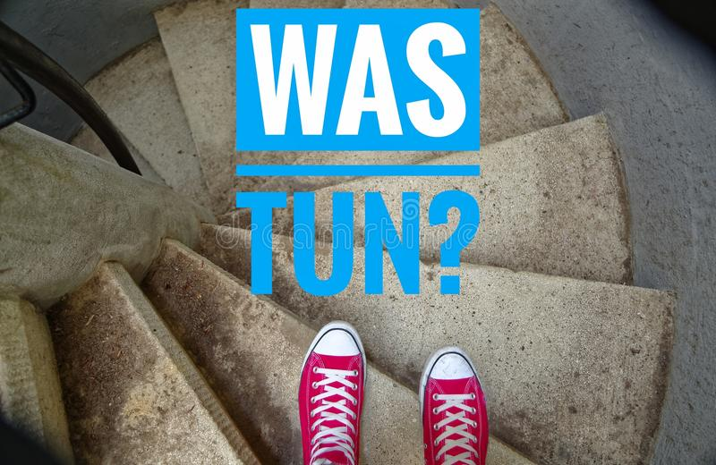 Red sneakers on spiral staircase when going downhill with inscription in german Was tun? in english What to do? royalty free stock images