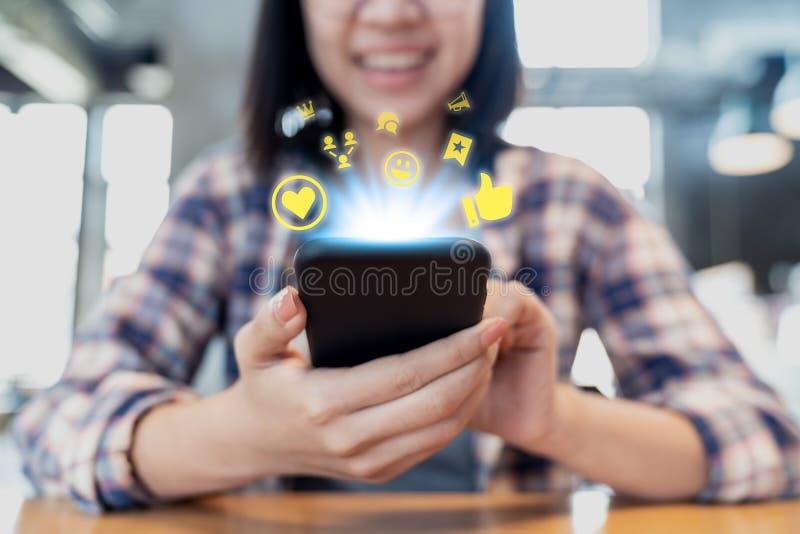 Red social de los medios del smartphone ascendente cercano que comparte y que comenta en comunidad en línea La mano de la mujer d foto de archivo