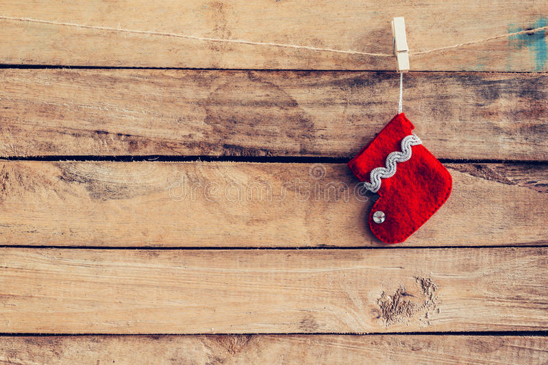 Red sock for Santa gifts hanging over rustic wooden background. stock images