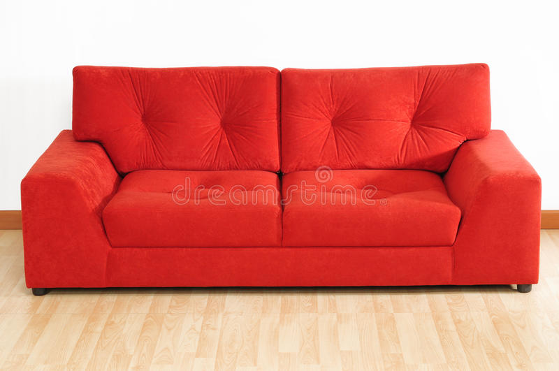 Red sofa. Comfortable red sofa on wooden floor royalty free stock photography