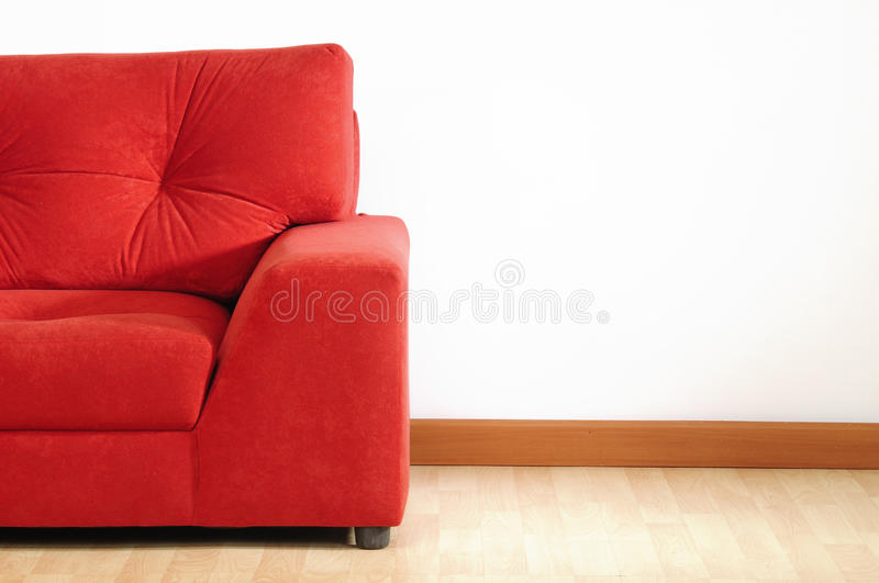 Red sofa. Comfortable red sofa on wooden floor royalty free stock photo