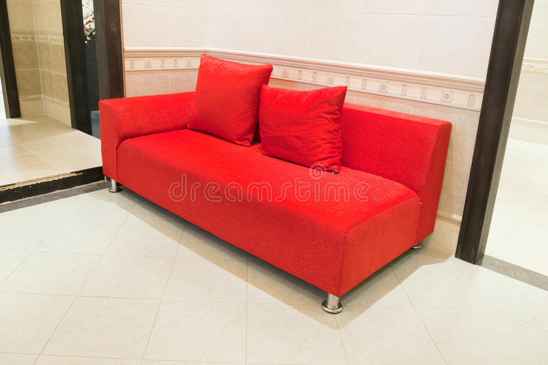 Red Sofa. On porcelain tile floor in an interior room royalty free stock photo