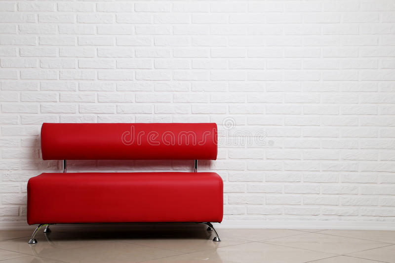 Red sofa. On a brick wall background royalty free stock image