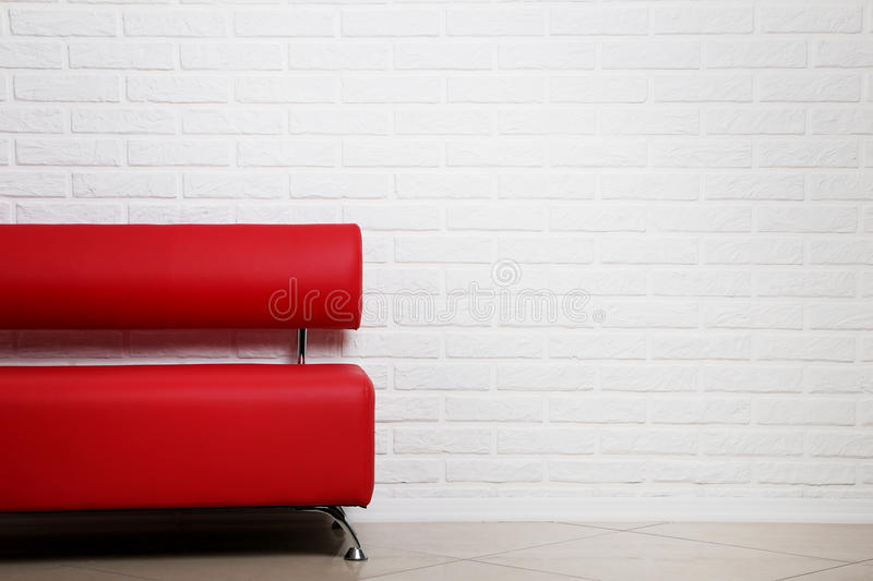 Red sofa. On a brick wall background stock photo