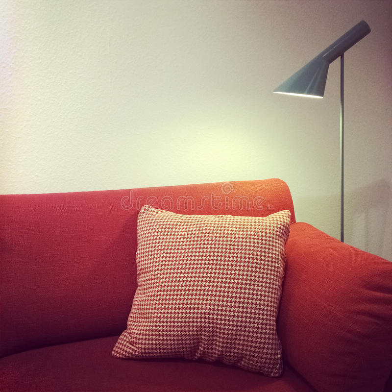 Red sofa with cushion and lamp. Detail of a living room red sofa and lamp. Modern furniture royalty free stock photography