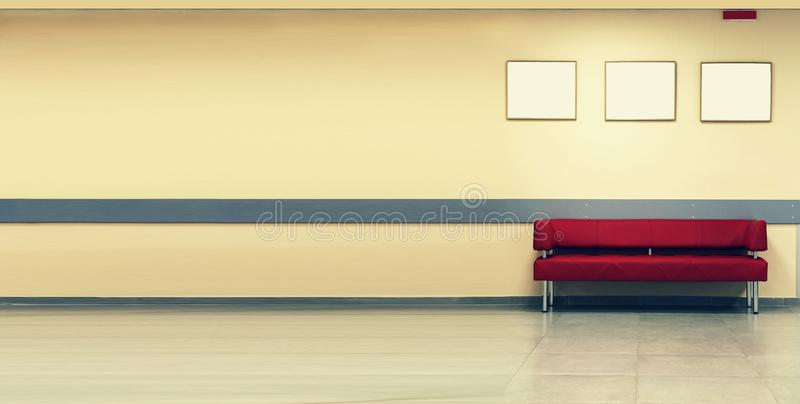 Style minimalism. Red Sofa, interior design, office. Empty waiting room with a modern red sofa in front of the door and three empt royalty free stock photos