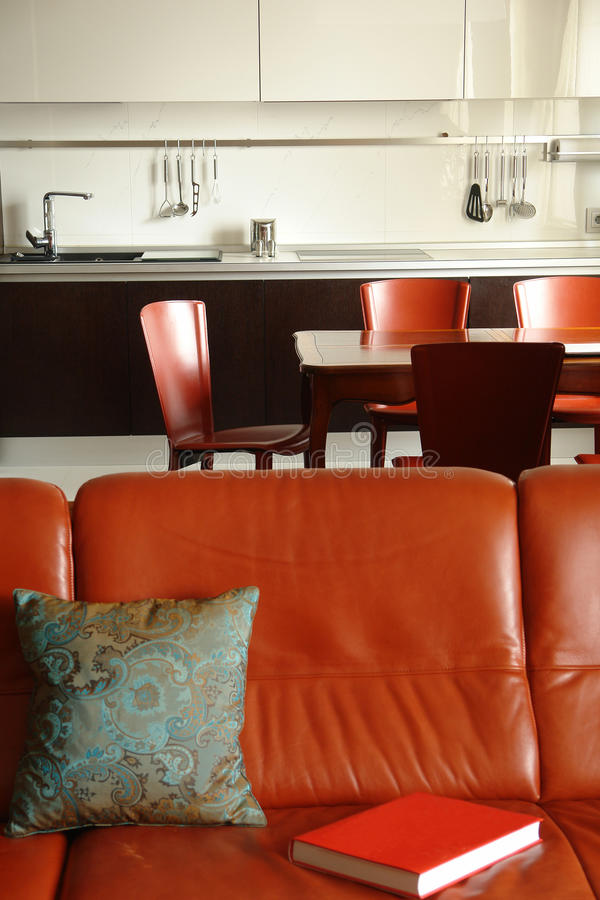 Red sofa and interior of a kitchen. With dinning place in red color royalty free stock photography