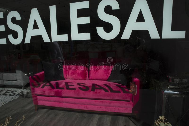 Red sofa in the shop window. Inscription on the glass - sale. The shadow of the inscription on the couch. stock photo
