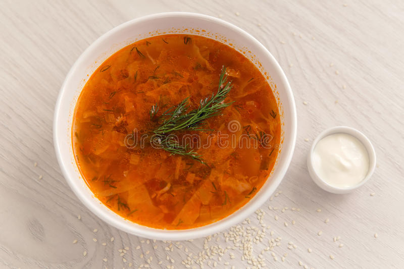 Red soup in white plate on the table with sour cream. In a white saucer stock photography