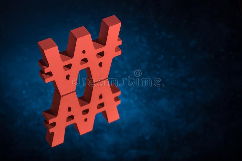 Red Won Symbol or Sign With Mirror Reflection on Blue Dusty Background. Red South Korean Currency Symbol or Sign Won With Mirror Reflection on Blue Dusty stock photography