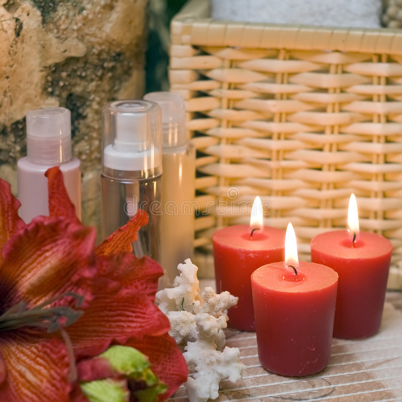 Red spa candles. A spa composition, some red candles, cosmetic bottles and red flower. Square format composition royalty free stock photo