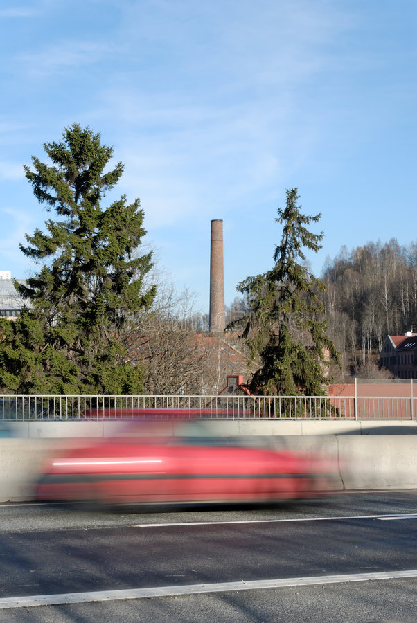 Red Speed. A red car zooming by on a highway bridge, set against a old factory pipe. Shot at Nydalen, Oslo, Norway stock photography