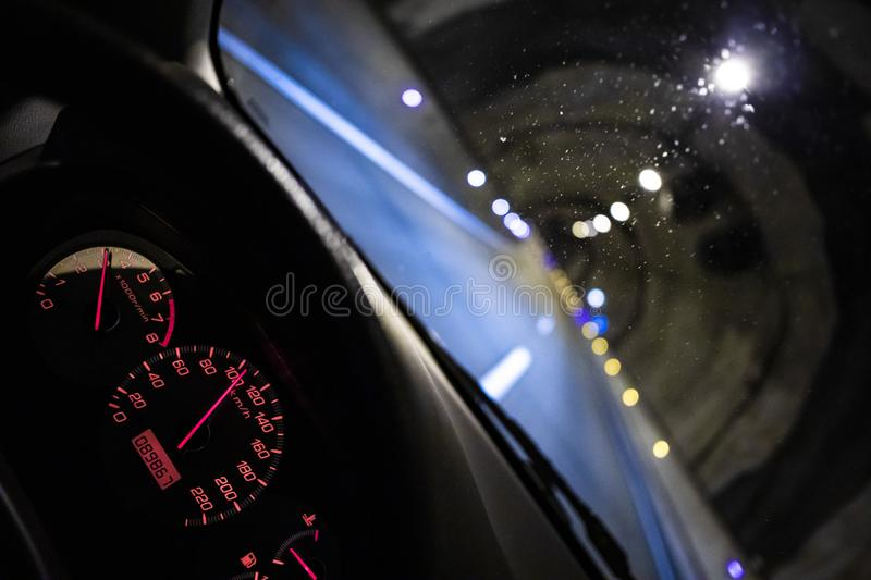 Red speedometer dash board inside a car cockpit stock image