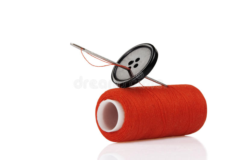 Red spool, black button and needle. Isolated on white background royalty free stock images