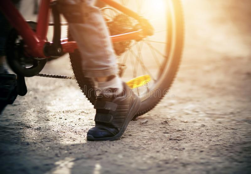 On a red sports bike rides a small child, pushing his foot  from the ground royalty free stock photography