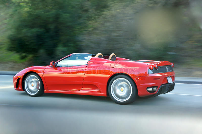 Red Sports Car Cruising on Highway. Fast car on CA freeway...snagged this shot from the backseat crammed between suitcases as brother drove us to airport. The stock image