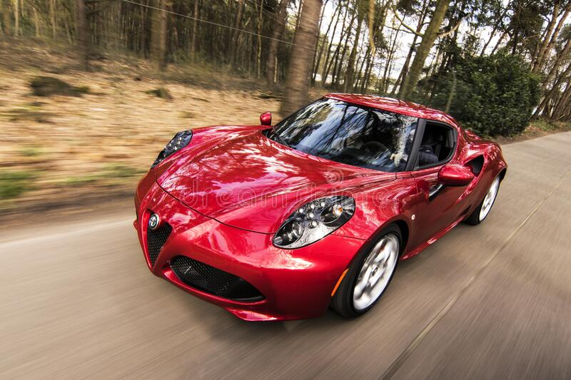 Red sports car on forest road stock photo