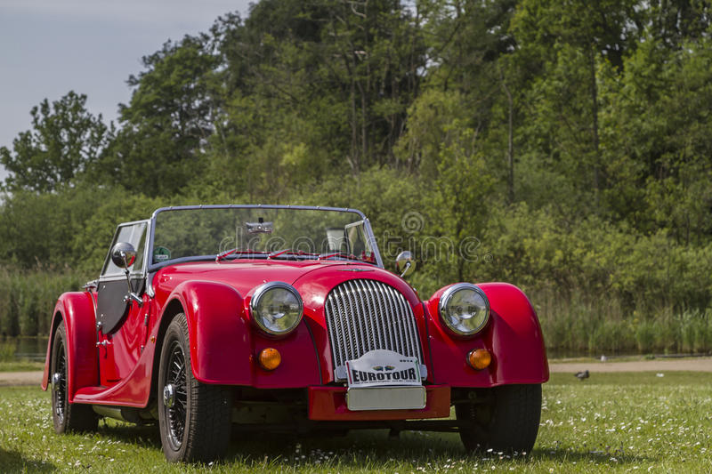 Red sports car. Morgan standing on meadow stock photo