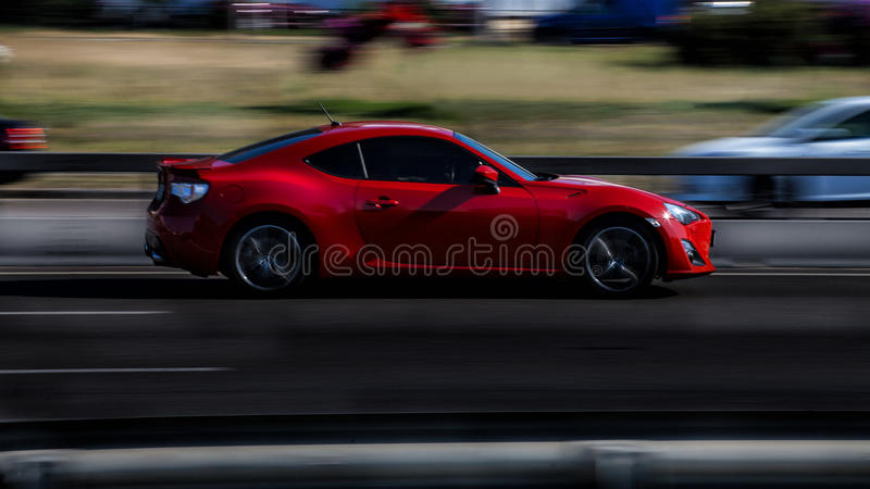 Red sports car. Subaru BRZ. Red sports car rides at high speed on the highway royalty free stock images