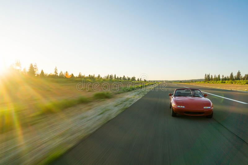 Red Sports Car Running on the Road Under Blue Sky during Daytime stock photo