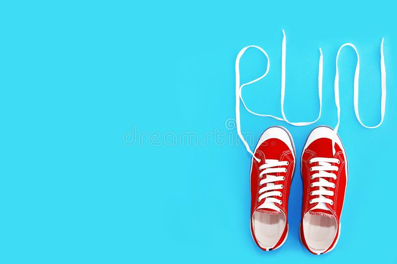 Red sports shoes sneakers with white laces and the word run royalty free stock photos