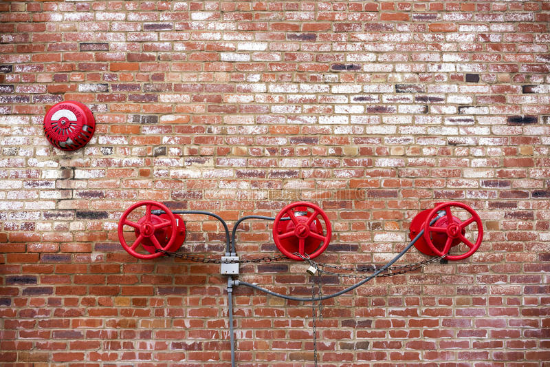 Red Sprinkler Valves against Red Brick Background. In an old building stock photography