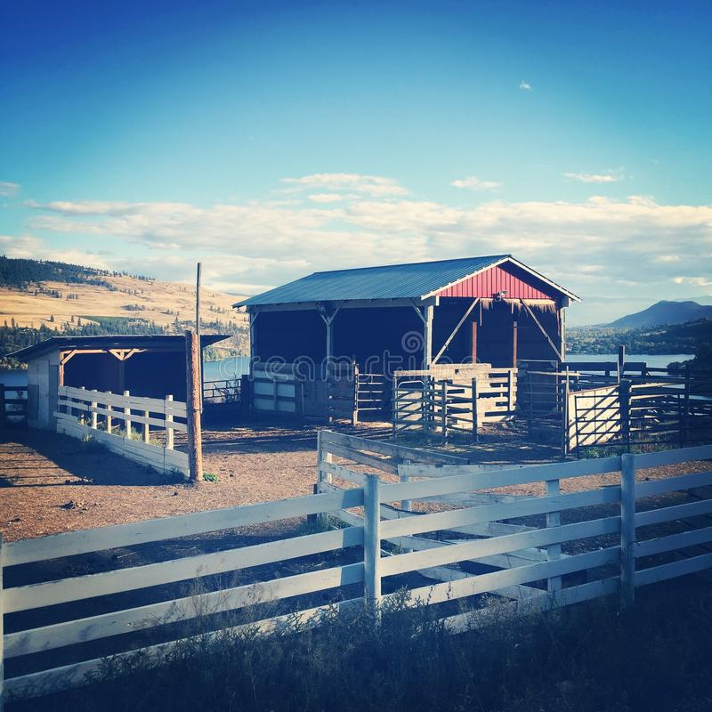 Red stable and white fence royalty free stock photography