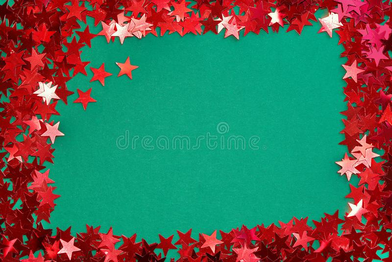Red star confetti on green background, Christmas frame. Shiny red confetti foil stars, border a green background. Suitable for a Christmas theme stock photo