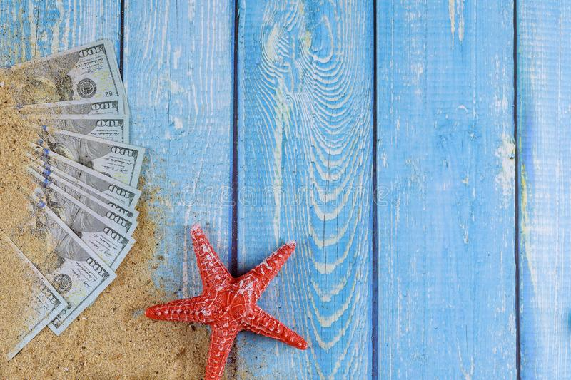 Red starfish on sand beach and US Dollar bill on blue wooden background. Red starfish on sand beach and US dollar bill on old blue wooden background royalty free stock photo