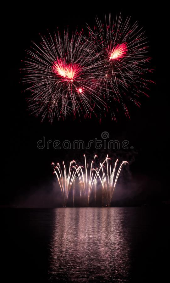 Red stars and gold fountain from rich fireworks over Brno`s Dam with lake reflection.  stock photo